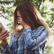 Image of a girl looking at her smartphone while covering her face with her other hand