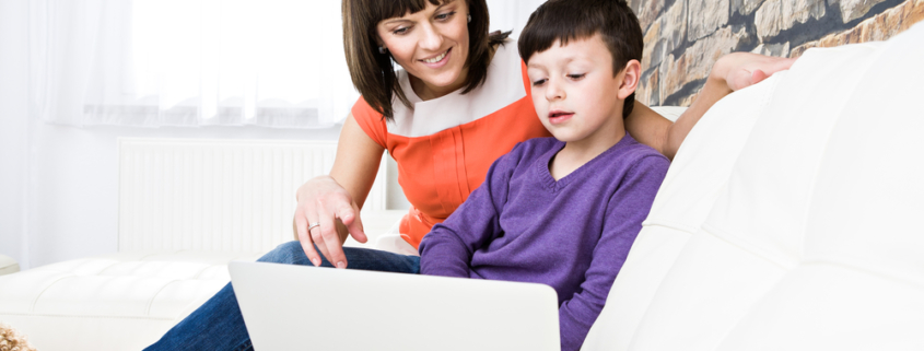 Image of a young boy sitting on the sofa with his mother in front of a laptop