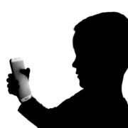 Silhouette of a young boy with a smartphone in his hands