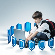 Image of a young boy sitting on the floor with his backpack on and typing on a laptop while being surrounded with small blue / silver shields.