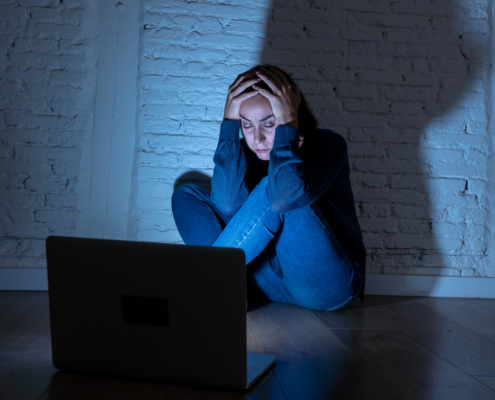 Image of a teen girl sitting in a dark room on the floor in front of the laptop holding her head in worry