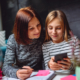 Image of a girl smiling while looking at her smartphone and showing it to her mother