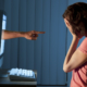 Image of a teen girl in front of a computer covering her face with her hands and a hand with a pointing index finger is coming out of the computer monitor