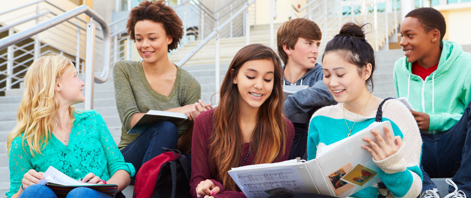 Image of a group of teens (4 girls and 2 boys) sitting on stairs in front of the school. 2 girls are reading some notes from the notebook and smiling, 2 boys are facing each other and smiling and the remaining 2 girls are facing each other and smiling.