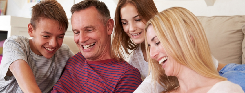 Image of a family (son, father, daughter and mother) all smiling and pointing at a smartphone