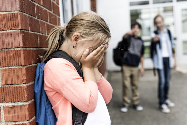 Image of a young girl against the wall and crying in her palms while two boys in the blurry background are pointing at her