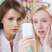 Image of mother and daughter looking worrying at the smartphone the daughter is holding in her right hand