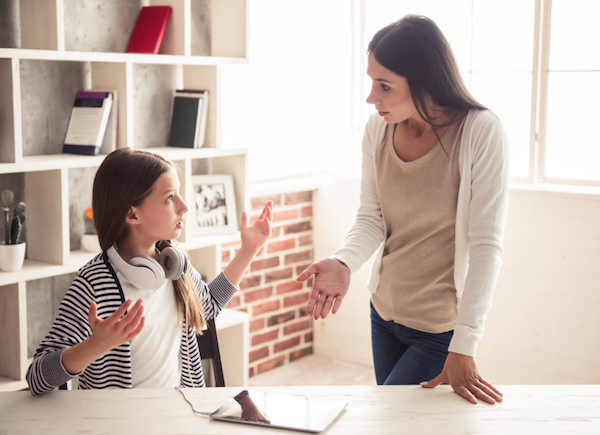 Image of a teen girl sitting down and possibly arguing with her mother who is standing next to her pointing to the iPad on the desk