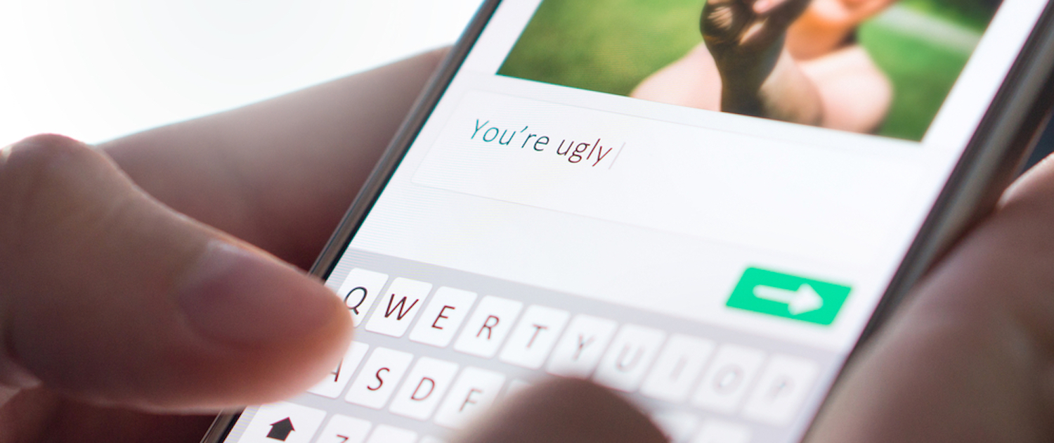 "Image of hands commenting on someone's picture ""You're uugly"" on their smartphones and are about the send the message"