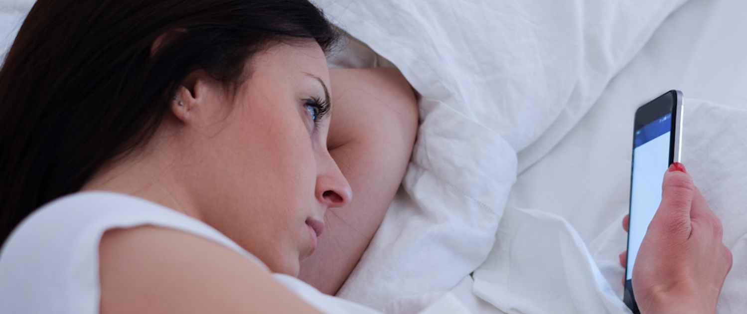 Image of a serious young woman lying in bed and looking at her smartphone