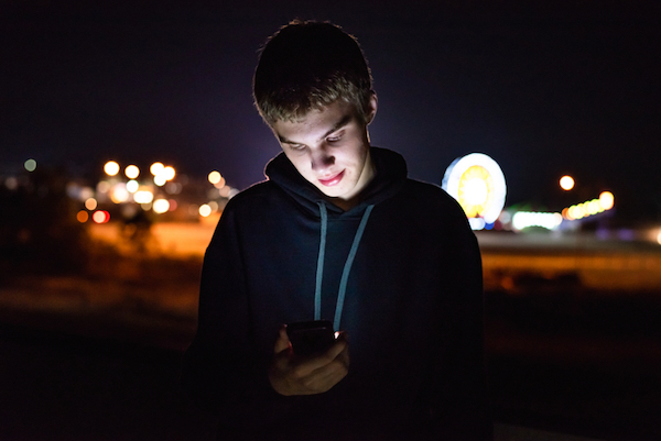 Image of a young teen boy looking at his mobile phone in the evening